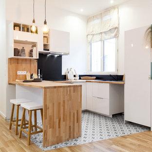 Küche in U-Form mit flächenbündigen Schrankfronten, weißen Schränken, Arbeitsplatte aus Holz, Küchenrückwand in Schwarz, Zementfliesen, Halbinsel und buntem Boden in Paris