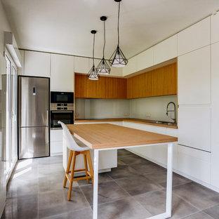 Réalisation d'une cuisine américaine parallèle design avec un évier posé, un placard à porte plane, des portes de placard blanches, un plan de travail en bois, une crédence beige, une crédence en feuille de verre, un électroménager en acier inoxydable, un îlot central, un sol gris et un plan de travail marron.