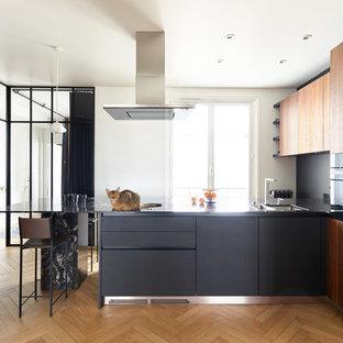 Réalisation d'une cuisine design en L avec un évier encastré, un placard à porte plane, des portes de placard en bois brun, une crédence noire, un électroménager noir, un sol en bois clair, une péninsule et un plan de travail noir.