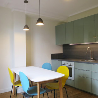 Inspiration for a mid-sized contemporary single-wall open plan kitchen in Paris with a single-bowl sink, flat-panel cabinets, green cabinets, laminate benchtops, grey splashback, slate splashback, white appliances, light hardwood floors, no island and beige floor.