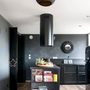 Mid-sized contemporary l-shaped separate kitchen in Other with black cabinets, black splashback, black appliances, light hardwood floors and a peninsula.