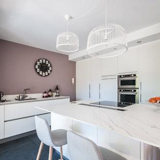 Cette photo montre une cuisine tendance avec un évier encastré, un placard à porte plane, des portes de placard blanches, un îlot central, un sol noir et un plan de travail blanc.