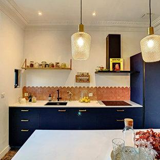 Ejemplo de cocina lineal, bohemia, grande, abierta, con fregadero bajoencimera, armarios con paneles lisos, puertas de armario azules, encimera de mármol, salpicadero rosa, salpicadero de azulejos de terracota, suelo de terrazo y una isla