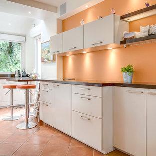 Aménagement d'une cuisine contemporaine avec un placard à porte plane, une crédence orange, un sol en carreau de terre cuite, une péninsule, un sol orange, un plan de travail marron, un électroménager en acier inoxydable, un évier 2 bacs, des portes de placard beiges et un plan de travail en bois.