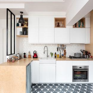 Inredning av ett skandinaviskt beige beige l-kök, med en rustik diskho, släta luckor, vita skåp, träbänkskiva, vitt stänkskydd, en halv köksö och grått golv