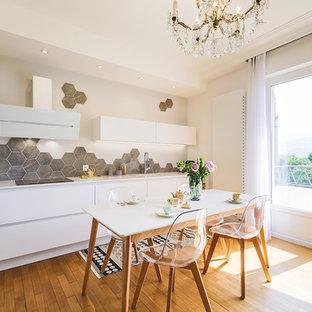 Idées déco pour une cuisine américaine scandinave avec un évier 1 bac, un placard à porte plane, des portes de placard blanches, une crédence grise, un sol en bois clair et un plan de travail blanc.