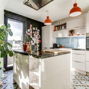 Cette image montre une cuisine nordique avec un placard à porte plane, des portes de placard blanches, une crédence bleue, une crédence en feuille de verre, un îlot central, un sol multicolore et un plan de travail noir.