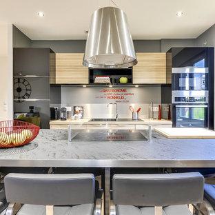 Zweizeilige, Mittelgroße Moderne Wohnküche mit Waschbecken, Laminat-Arbeitsplatte, Laminat, Kücheninsel, Kassettenfronten, Edelstahlfronten, Küchenrückwand in Grau, Rückwand aus Metallfliesen, Küchengeräten aus Edelstahl, grauem Boden und beiger Arbeitsplatte in Paris