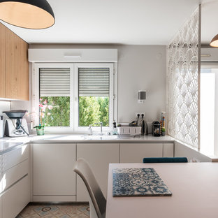 Photo of a mid-sized scandinavian u-shaped kitchen in Lyon with an integrated sink, white cabinets, quartzite benchtops, white splashback, glass sheet splashback, stainless steel appliances, cement tiles, no island, beige floor and white benchtop.