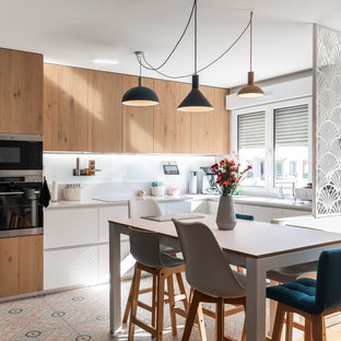 Inspiration for a medium sized scandinavian kitchen/diner in Lyon with quartz worktops, white splashback, glass sheet splashback, stainless steel appliances, cement flooring, no island, white worktops, flat-panel cabinets, light wood cabinets and multi-coloured floors.