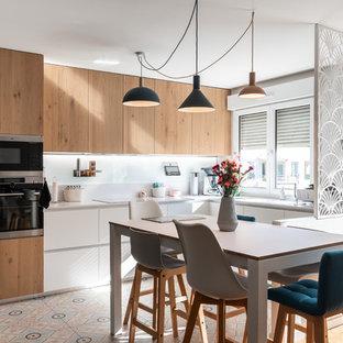 リヨンの中くらいの北欧スタイルのおしゃれなダイニングキッチン (珪岩カウンター、白いキッチンパネル、ガラス板のキッチンパネル、シルバーの調理設備、セメントタイルの床、アイランドなし、白いキッチンカウンター、フラットパネル扉のキャビネット、淡色木目調キャビネット、マルチカラーの床) の写真