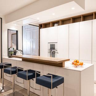 Idées déco pour une cuisine contemporaine avec un placard à porte plane, des portes de placard blanches, un électroménager blanc, un îlot central, un sol beige et un plan de travail blanc.