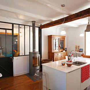 Réalisation d'une cuisine linéaire bohème fermée et de taille moyenne avec un évier 2 bacs, un placard à porte plane, des portes de placard blanches, un sol en bois brun et un îlot central.
