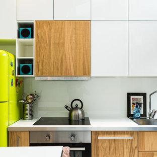 ボルドーの小さいコンテンポラリースタイルのおしゃれなキッチン (シングルシンク、フラットパネル扉のキャビネット、白いキャビネット、ラミネートカウンター、白いキッチンパネル、ガラスタイルのキッチンパネル、パネルと同色の調理設備、塗装フローリング、白い床、白いキッチンカウンター) の写真