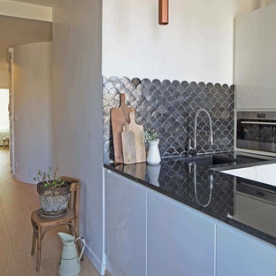 Kleine Moderne Wohnküche ohne Insel in L-Form mit integriertem Waschbecken, Kassettenfronten, weißen Schränken, Granit-Arbeitsplatte, Küchenrückwand in Schwarz und Rückwand aus Terrakottafliesen in Marseille