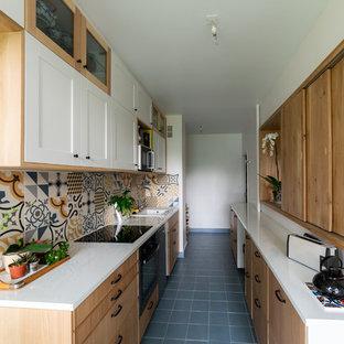 Esempio di una cucina lineare chic di medie dimensioni con top in laminato, top bianco, lavello da incasso, ante in stile shaker, ante in legno chiaro, paraspruzzi multicolore, paraspruzzi con piastrelle a mosaico, elettrodomestici neri, nessuna isola e pavimento nero