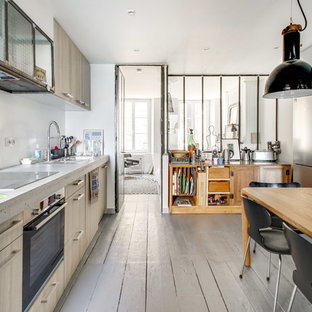 This is an example of a scandinavian eat-in kitchen in Le Havre with flat-panel cabinets, light wood cabinets, concrete benchtops, painted wood floors, beige floor and grey benchtop.