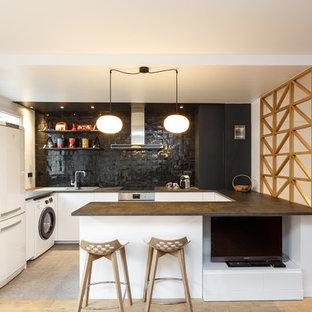 Exemple d'une cuisine ouverte scandinave en U de taille moyenne avec un placard à porte plane, des portes de placard blanches, un plan de travail en stratifié, une crédence noire, une crédence en carreau de terre cuite, un sol en carrelage de porcelaine, un sol gris, un évier posé, un électroménager blanc, une péninsule et un plan de travail noir.