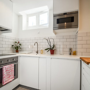 Small scandinavian enclosed kitchen designs - Enclosed kitchen - small scandinavian u-shaped enclosed kitchen idea in Paris with a drop-in sink, flat-panel cabinets, white cabinets, white backsplash, subway tile backsplash, stainless steel appliances and no island