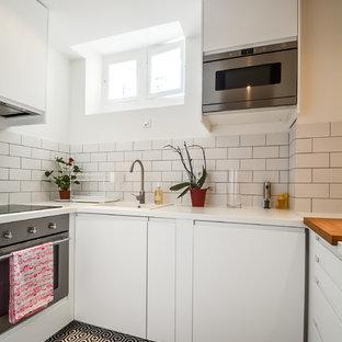 Aménagement d'une petite cuisine scandinave en U fermée avec un évier posé, un placard à porte plane, des portes de placard blanches, une crédence blanche, une crédence en carrelage métro, un électroménager en acier inoxydable et aucun îlot.