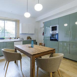 Exemple d'une cuisine américaine tendance avec un évier encastré, un placard à porte plane, des portes de placards vertess, une crédence blanche, un sol en bois clair, un sol beige et un plan de travail blanc.