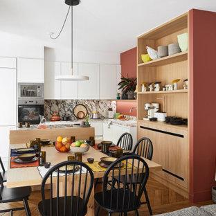 Idées déco pour une cuisine américaine contemporaine en L de taille moyenne avec un évier posé, un placard à porte plane, des portes de placard blanches, une crédence grise, un électroménager encastrable, un îlot central, un sol marron et un plan de travail gris.