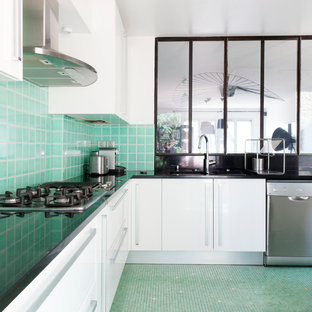 This is an example of a large industrial l-shaped separate kitchen in Paris with white cabinets, green splashback and no island.