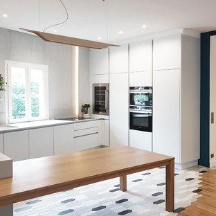 Idées déco pour une cuisine scandinave en U avec un évier encastré, un placard à porte plane, des portes de placard blanches, un électroménager noir, une péninsule, un sol gris et un plan de travail gris.