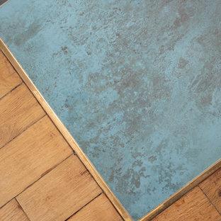 パリの小さい地中海スタイルのおしゃれなキッチン (アンダーカウンターシンク、フラットパネル扉のキャビネット、淡色木目調キャビネット、青いキッチンパネル、セラミックタイルのキッチンパネル、黒い調理設備、セラミックタイルの床、青い床、黒いキッチンカウンター、人工大理石カウンター) の写真
