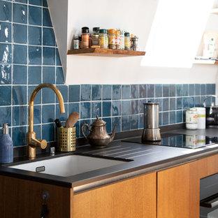 他の地域の小さい地中海スタイルのおしゃれなキッチン (フラットパネル扉のキャビネット、淡色木目調キャビネット、青いキッチンパネル、セラミックタイルのキッチンパネル、黒い調理設備、セラミックタイルの床、青い床、黒いキッチンカウンター、アンダーカウンターシンク、人工大理石カウンター) の写真