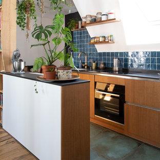 他の地域の小さいエクレクティックスタイルのおしゃれなキッチン (フラットパネル扉のキャビネット、青いキッチンパネル、セラミックタイルのキッチンパネル、黒い調理設備、セラミックタイルの床、青い床、黒いキッチンカウンター、中間色木目調キャビネット、アンダーカウンターシンク、人工大理石カウンター) の写真