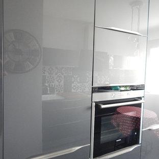 リヨンの中サイズのエクレクティックスタイルのおしゃれなキッチン (アンダーカウンターシンク、フラットパネル扉のキャビネット、グレーのキャビネット、ラミネートカウンター、マルチカラーのキッチンパネル、セラミックタイルのキッチンパネル、セラミックタイルの床、黒い床) の写真