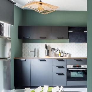 Inspiration pour une petit cuisine américaine linéaire design avec un évier encastré, un plan de travail en bois, un sol en vinyl, un sol gris, un placard à porte plane, des portes de placard noires, une crédence blanche, un électroménager en acier inoxydable, aucun îlot et un plan de travail beige.