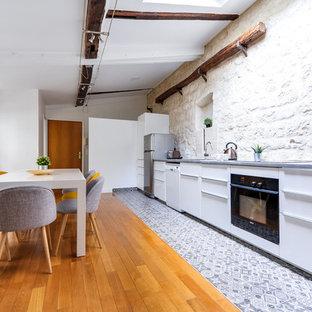 Idée de décoration pour une cuisine américaine linéaire design avec un placard à porte plane, des portes de placard blanches, un sol en bois clair, aucun îlot, un sol marron et un plan de travail gris.