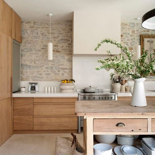 Aménagement d'une grande cuisine parallèle campagne fermée avec un îlot central et des portes de placard en bois clair.
