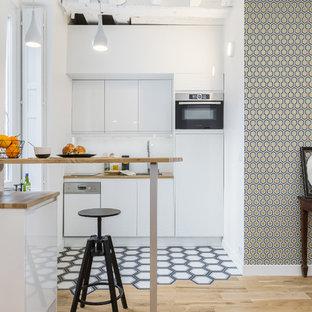Idée de décoration pour une cuisine linéaire nordique de taille moyenne avec un évier posé, un placard à porte plane, des portes de placard blanches, un plan de travail en bois, une crédence blanche, un électroménager blanc, une péninsule, un plan de travail marron et un sol en bois clair.