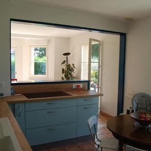 パリの中サイズのカントリー風おしゃれなキッチン (木材カウンター、テラコッタタイルの床、オレンジの床、フラットパネル扉のキャビネット、青いキャビネット、ベージュキッチンパネル、木材のキッチンパネル、アイランドなし、ベージュのキッチンカウンター、アンダーカウンターシンク、パネルと同色の調理設備) の写真
