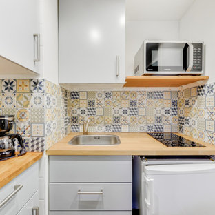Small eclectic l-shaped open plan kitchen in Lyon with an undermount sink, beaded inset cabinets, grey cabinets, wood benchtops, multi-coloured splashback, cement tile splashback, white appliances, linoleum floors, no island, grey floor and beige benchtop.