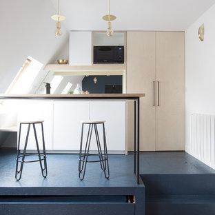 Exemple d'une petite cuisine ouverte parallèle tendance avec un placard à porte plane, des portes de placard en bois clair, une crédence noire, une crédence en feuille de verre, une péninsule, un sol bleu, un évier 1 bac, un plan de travail en bois, un électroménager noir et béton au sol.