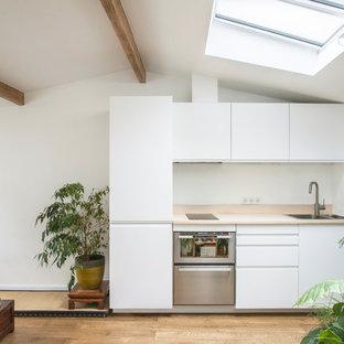 Inspiration pour une petit cuisine ouverte linéaire nordique avec un évier posé, un placard à porte plane, des portes de placard blanches, un électroménager en acier inoxydable, un sol en bois clair, aucun îlot et un plan de travail beige.