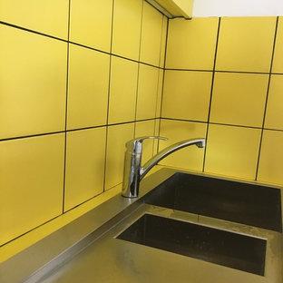 Foto di una piccola cucina moderna con lavello sottopiano, top in laminato, paraspruzzi giallo, paraspruzzi con piastrelle in ceramica, elettrodomestici neri, pavimento con piastrelle in ceramica, nessuna isola, pavimento nero e top giallo