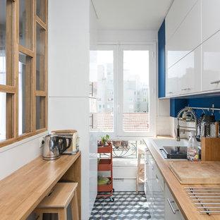 Idée de décoration pour une cuisine linéaire nordique fermée avec un évier posé, un placard à porte plane, des portes de placard blanches, un plan de travail en bois, une crédence blanche, une crédence en carrelage métro, un électroménager blanc, aucun îlot, un sol multicolore et un sol en carreaux de ciment.