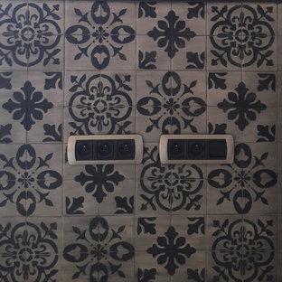Modelo de cocina en L, urbana, de tamaño medio, cerrada, con fregadero bajoencimera, puertas de armario negras, encimera de acero inoxidable, salpicadero negro, salpicadero de piedra caliza, electrodomésticos de acero inoxidable, suelo vinílico, suelo gris, encimeras negras y una isla