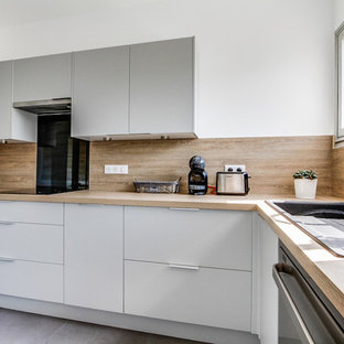 Large scandinavian l-shaped separate kitchen in Paris with a single-bowl sink, beaded inset cabinets, grey cabinets, laminate benchtops, beige splashback, black appliances, ceramic floors, no island, grey floor and beige benchtop.