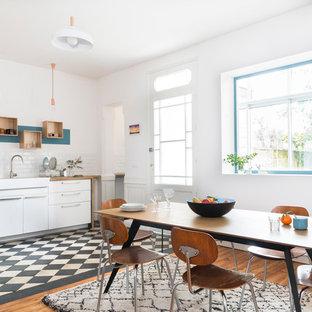 Inspiration pour une grande cuisine américaine linéaire nordique avec un évier de ferme, un placard à porte plane, des portes de placard blanches, un plan de travail en bois, une crédence blanche, un sol en bois brun et aucun îlot.