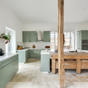 Design ideas for a large eclectic l-shaped open plan kitchen in Paris with an undermount sink, flat-panel cabinets, green cabinets, laminate benchtops, white splashback, subway tile splashback, panelled appliances, marble floors, with island and beige floor.