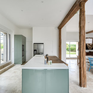 Inspiration for a large eclectic l-shaped open plan kitchen in Paris with an undermount sink, flat-panel cabinets, green cabinets, laminate benchtops, white splashback, subway tile splashback, panelled appliances, marble floors, with island and beige floor.