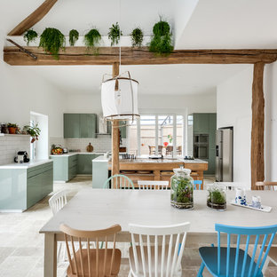 Photo of a large eclectic l-shaped open plan kitchen in Paris with an undermount sink, flat-panel cabinets, green cabinets, laminate benchtops, white splashback, subway tile splashback, panelled appliances, marble floors, with island and beige floor.