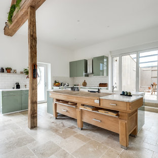 This is an example of a large eclectic l-shaped open plan kitchen in Paris with an undermount sink, flat-panel cabinets, green cabinets, laminate benchtops, white splashback, subway tile splashback, panelled appliances, marble floors, with island and beige floor.