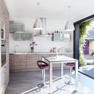 Idée de décoration pour une grande cuisine américaine design en L avec un placard à porte plane, des portes de placard en bois brun, un plan de travail en stratifié, béton au sol, un îlot central et un électroménager en acier inoxydable.